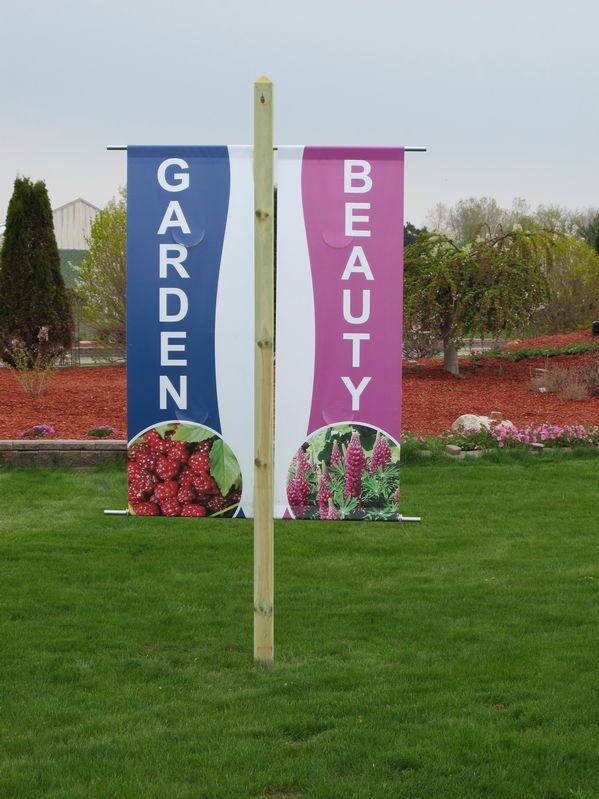 Large, easy-to-read roadside banners for Garden Crossings in Zeeland, MI get drivers' attention. There are four banners and each one has a different plant picture to show a variety of plants offered.